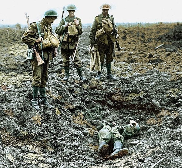 Two soldiers stand looking at the body of a fallen comrade