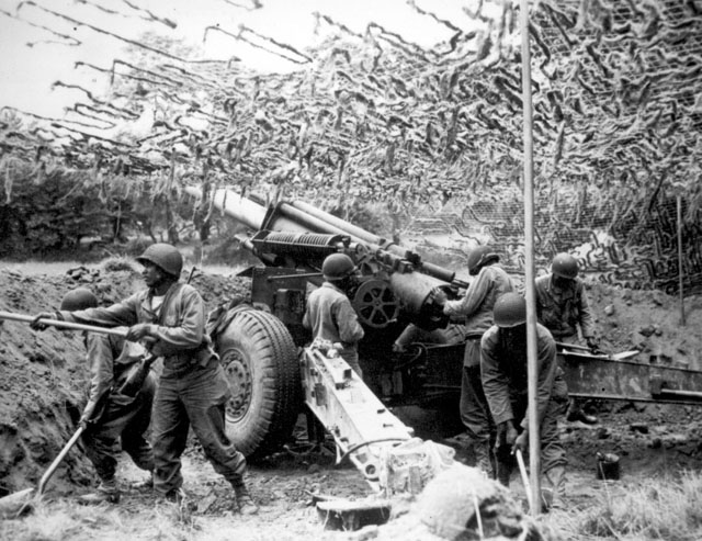 African-American troops of a field artillery battery set up a 155mm howitzer in France (June 28, 1944).
