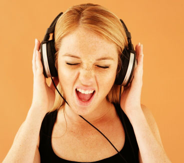 person holding their headphones while listening to music