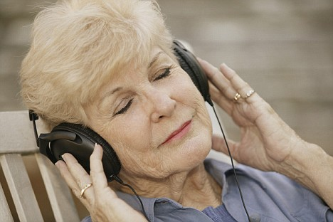 people holding their headphones while listening to music